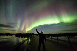 Tourist under Northern Lights